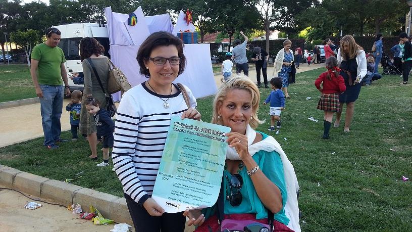 Ana María Soria y Alicia García, Secretaria y Vocal de la A.V.V. Gran Vía posan con el cartel del III Ciclo de Títeres de San Pablo - Santa Justa