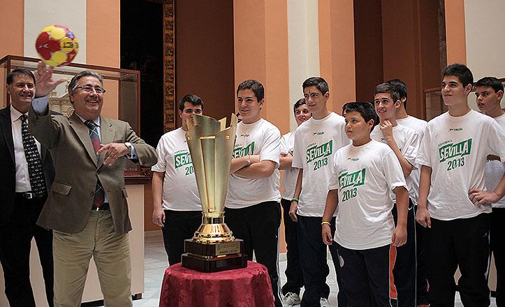 El alcalde, Juan Ignacio Zoido, pasa el balón del Mundial de balonmano a un jugador del Club de Utrera