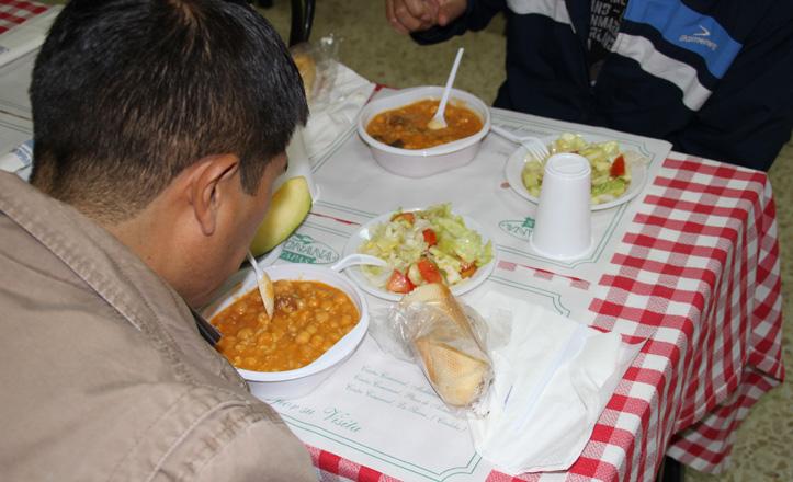 Un hombre comiendo un plato de garbanzos en el comedor