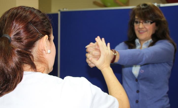 La rehabilitadora de la Asociación haciendo un ejercicio con una paciente
