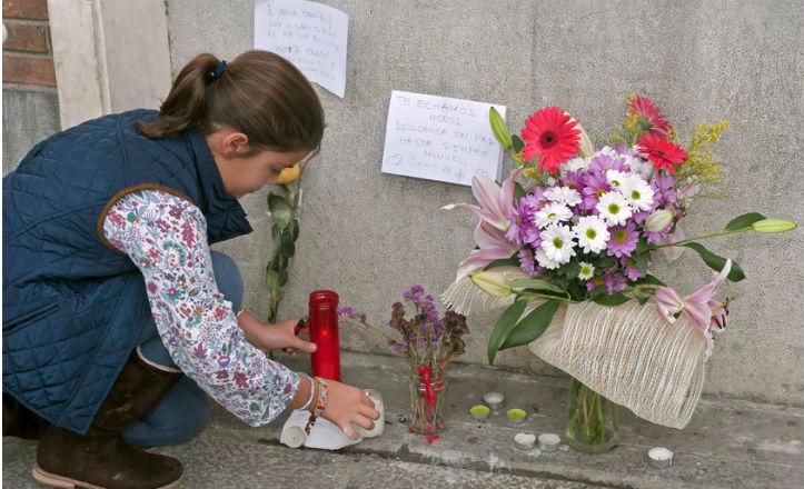 Una vecina pequeña enciende una vela por Manuel / JOSÉ LUCAS