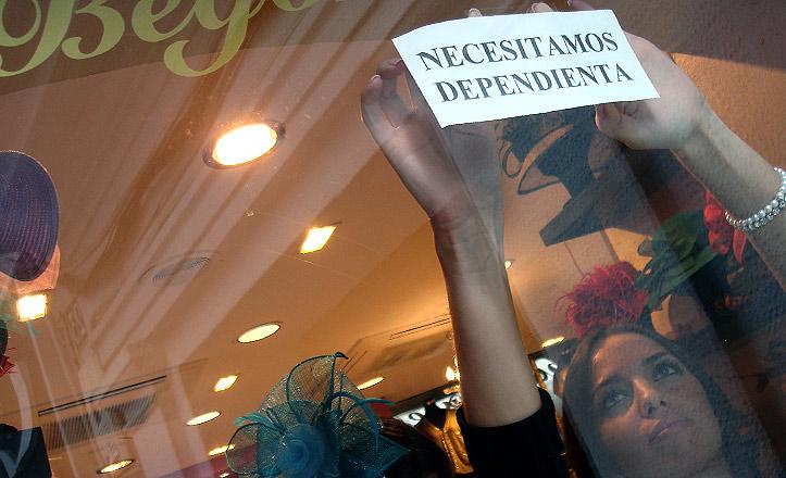 Una chica coloca un cartel en un escaparate donde dice que se necesita dependienta.