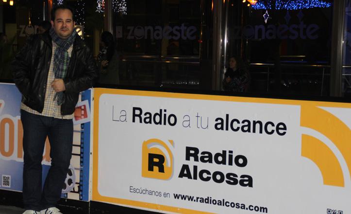Álvaro Martín posa junto al cartel de Radio Alcosa de la pista de hielo de Zona Este