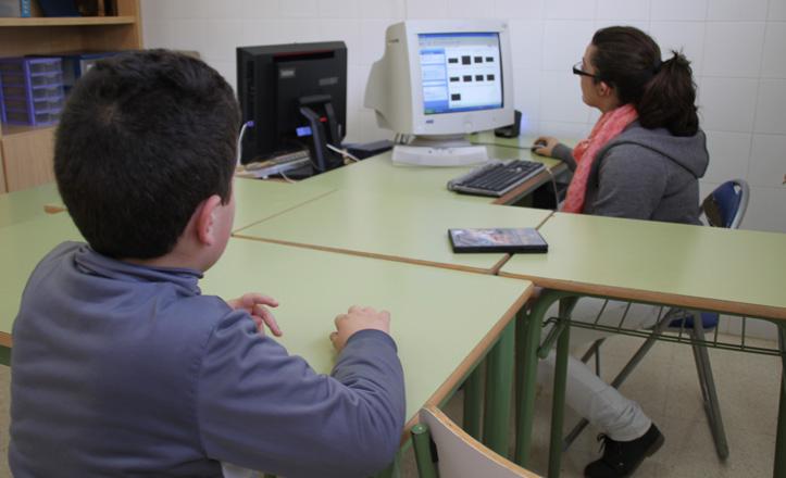 Un alumno de unos ocho años con su profesora viendo algo en el ordenador