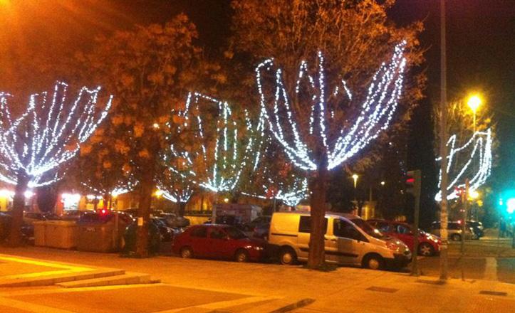 Una de las calles del distrito con luces en los árboles