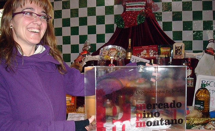 La presidenta de la Asociación del mercado de Pino Montano con la cesta de Navidad.