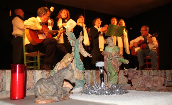 Un Nacimiento colocado a los pies del escenario. De fondo, la actuación del coro La Fragua