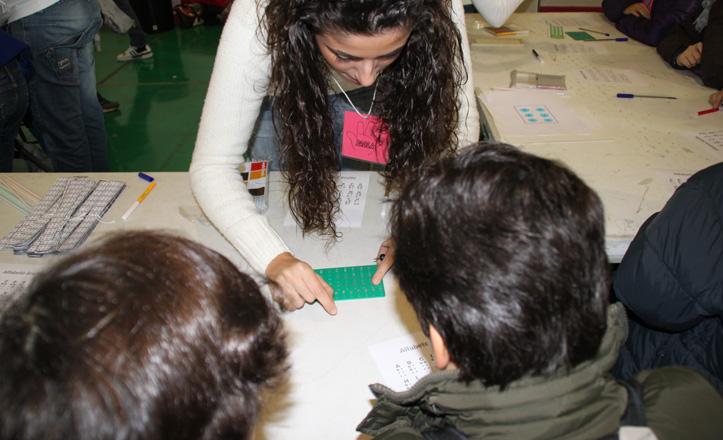 Una de las monitoras enseñando braille a un grupo de niños