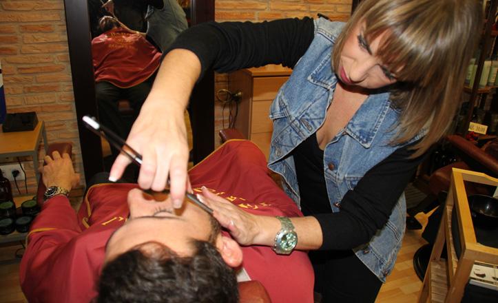 Virginia afeitando a uno de sus clientes