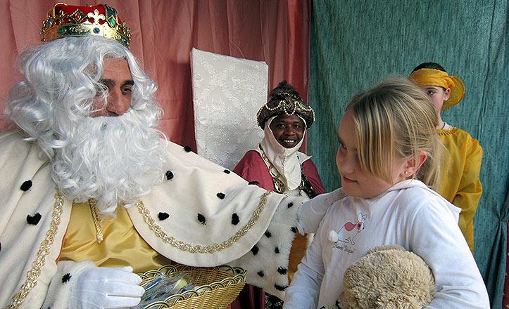 El Rey Melchor , muy parecido al delegado del Distrito Norte, Juan García, da un regalo a una niña.