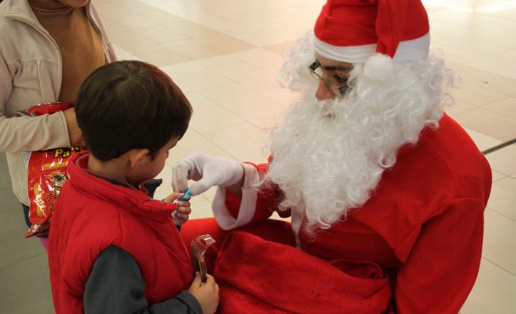 Papá Noel da un caramelo a un niño