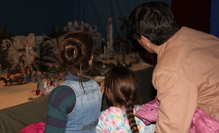 Dos niñas con su padre viendo un belén