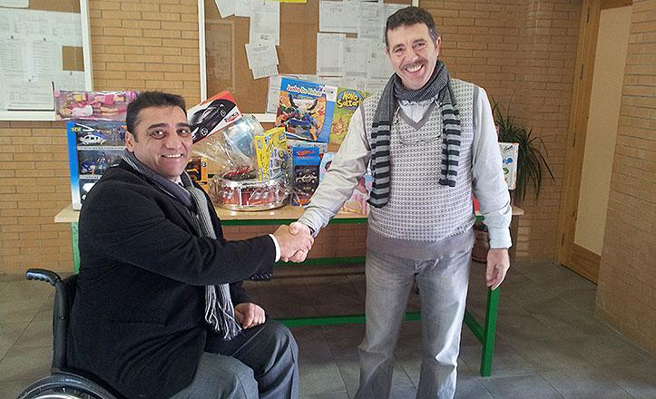 Juan García entrega los juguetes al director del colegio Sagrada Familia de Valdezorras