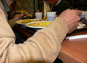 Un usuario come en el comedor de San Juan de Dios de Sevilla