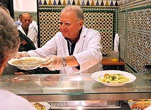 Un voluntario sirve un plato a un usuario en el comedor de San Juan de Dios