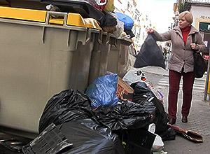 Una mujer deja la basura en el contenedor