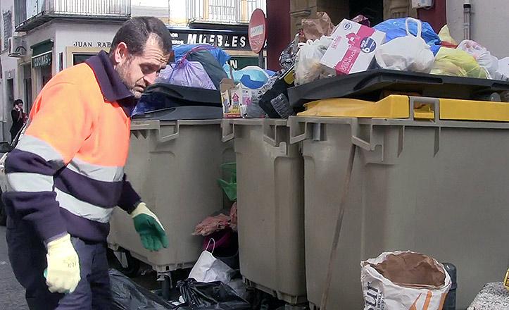 Los servicios mínimos de Lipasam recogen la basura desbordada de los contenedores.