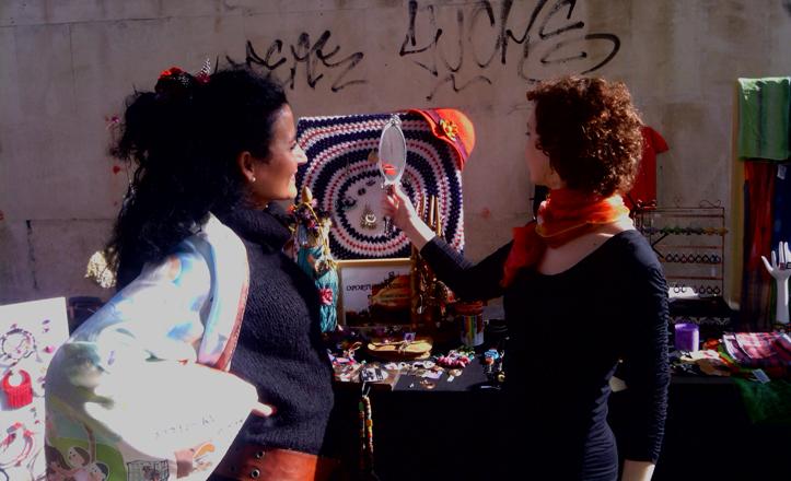 En uno de los expositores una chica se mira a un espejo viendo como queda uno de los pañuelos que va a comprar