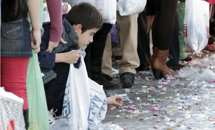 Un niño recogiendo caramelos en la cabalgata