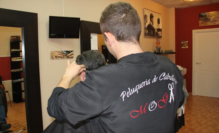 Manuel cortando el pelo a uno de sus clientes