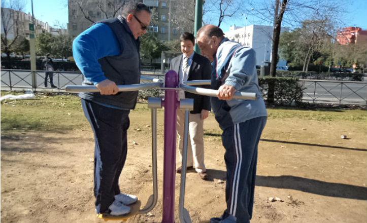 El delegado del distrito Sur, junto a dos vecinos que prueban los aparatos de gimnasia