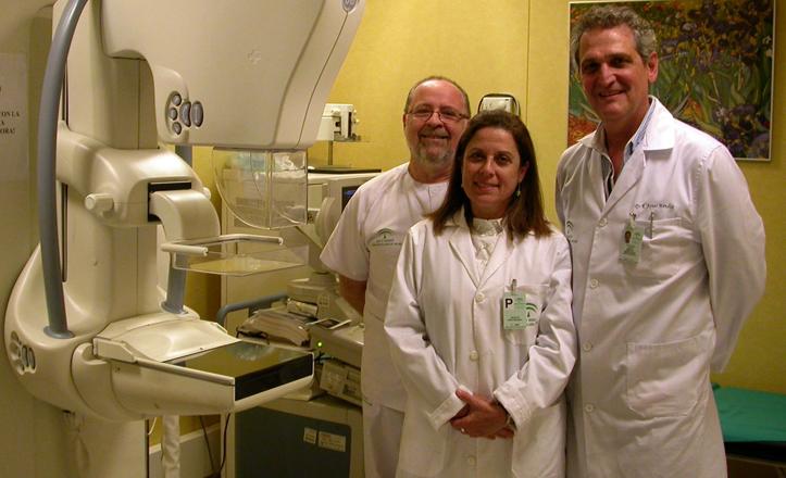 Médicos del hospital posan junto a un mamógrafo