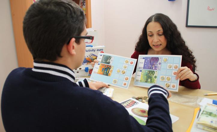 Esperanza enseña las monedas a uno de sus niños