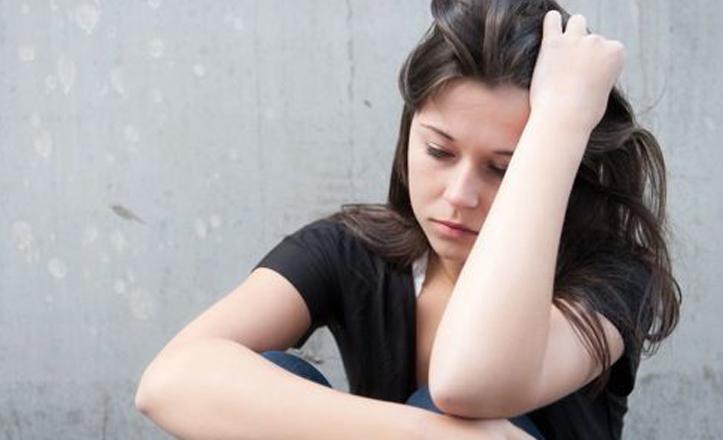 Imagen recurso de una joven sentada en el suelo con gesto de preocupación