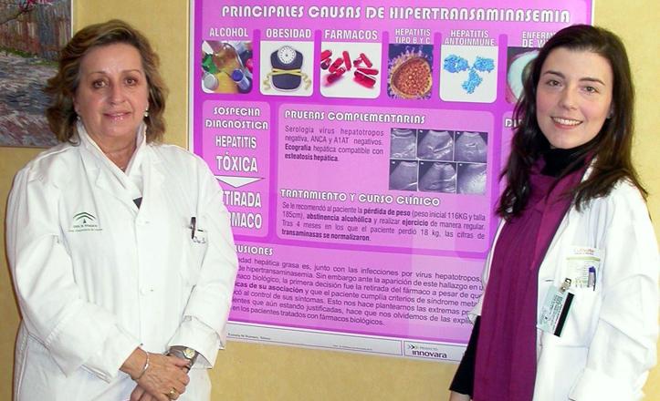 Las galardonadas posan delante del cartel de su estudio clínico