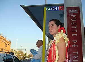 Una joven espera el autobús en la parada del Puente de Triana