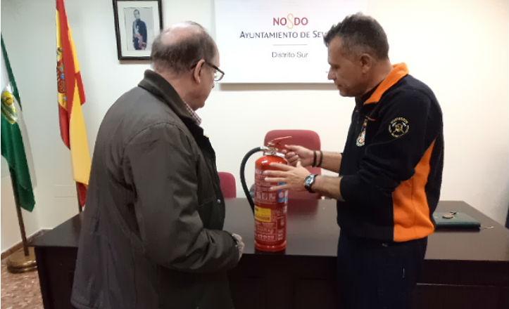 Javier Rivas, presidente de SOS Ayudas sin fronteras, explicando a un vecino del distrito Sur como usar un extintor