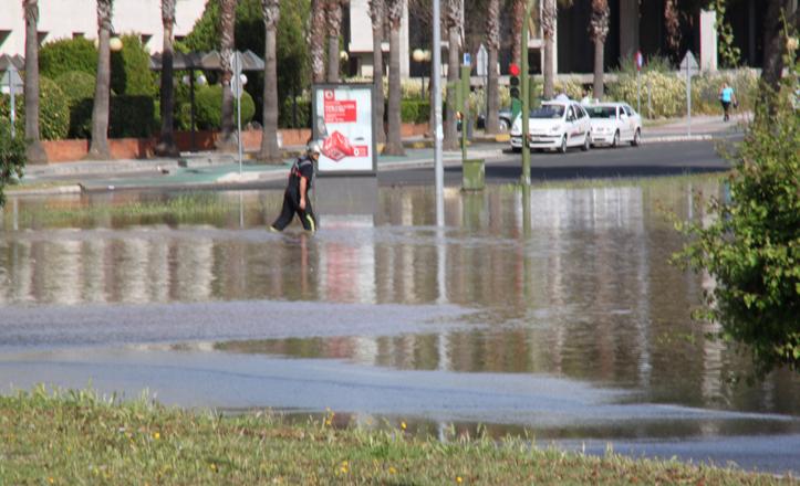 Un bombero atraviesa la calle, el agua le llega por encima de las rodillas