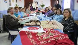Las alumnas del taller de bordado posan con sus trabajos