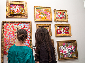 Dos chicas observan los cuadros de Olek