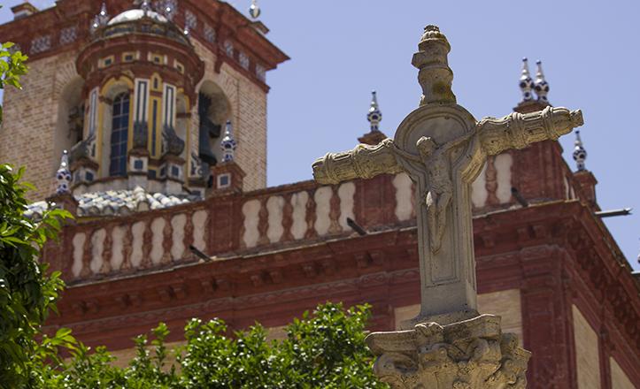 El crucifijo de la plaza de Teresa Enríquez recorta su silueta entre las cubiertas de San Vicente y los naranjos del lugar
