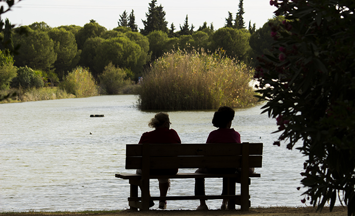 Dos mujeres conversan relejadas frente a la laguna del Parque Infanta Elena / Fran Piñero