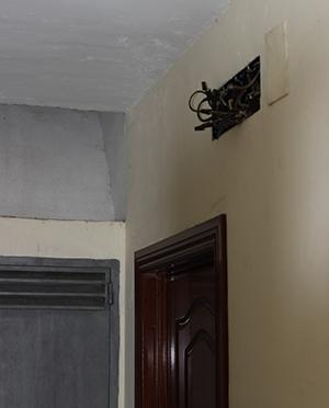 Contador y cables a la vista, junto a la puerta de las viviendas sociales de los Bermejales / Fran Piñero