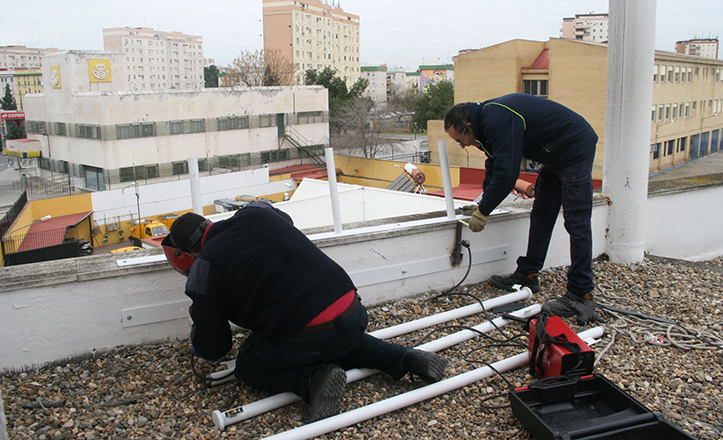 Operarios cambiando los mástiles de la fachada del Distrito San Pablo-Santa Justa