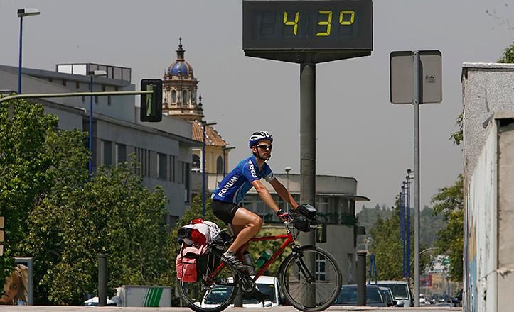 Un ciclista en bici junto a un termómetro que marca 43 grados